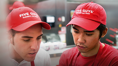 Two Five Guys workers are having a conversation.
