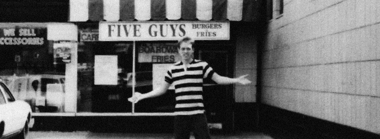 One of the Five Guys standing in front of one of the company's first restaurants.